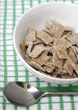 Breakfast Cereal Shreddies. Healthy breakfast cereal in bowl on kitchen cloth with spoon Royalty Free Stock Image