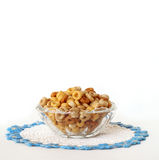 Breakfast Cereal in a Vintage Glass Bowl Isolated on White. A bowl of multi-grain breakfast cereal sitting in a vintage glass bowl and sitting on a crocheted Royalty Free Stock Photo