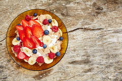 Breakfast cereal in yogurt. Top view. Strawberries, blueberries, bananas and breakfast cereal in yogurt on a wooden rustic table with copy space royalty free stock image