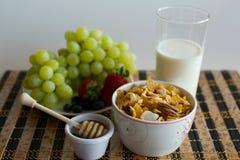 Breakfast cereals. Corn flakes with fruit, honey and milk - healthy breakfast Stock Image