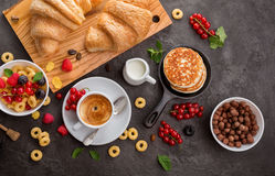 Breakfast cereals, croissants, fresh berries and cup of coffee. Breakfast cereals, french croissants, fresh berries and cup of coffee. Healthy food concept Stock Image