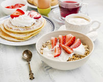 Breakfast with cereals, yogurt and strawberries, coffee cup and Royalty Free Stock Photo