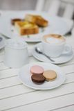 Breakfast with cheesecakes, toast, cappuccino and macarons Stock Images