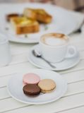Breakfast with cheesecakes, toast, cappuccino and macarons Royalty Free Stock Photography