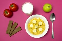 Breakfast child in school, corn flakes with milk, apple, bread on pink background stock photo