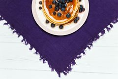 Christmas pancakes with honey and blueberries on a violet napkin. Breakfast for children with pancakes, honey and blueberries. Christmas pancakes with honey and Royalty Free Stock Photos