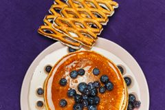 Christmas pancakes with honey and blueberries on a violet napkin. Breakfast for children with pancakes, honey and blueberries. Christmas pancakes with honey and Royalty Free Stock Photo