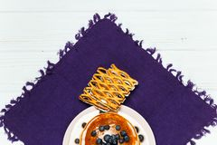 Christmas pancakes with honey and blueberries on a violet napkin. Breakfast for children with pancakes, honey and blueberries. Christmas pancakes with honey and Stock Photos