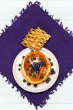 Christmas pancakes with honey and blueberries on a violet napkin. Breakfast for children with pancakes, honey and blueberries. Christmas pancakes with honey and Stock Photography