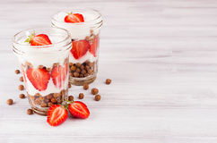 Breakfast with chocolate balls corn flakes, sliced strawberry in jars on white wood board. Decorative border with copy space. Royalty Free Stock Photo