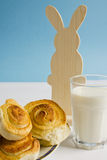 Breakfast with cinnamon buns and glass of milk on a blue background with decoration Easter bunny. Stock Photo