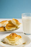Breakfast with cinnamon buns and glass of milk on a blue background. Royalty Free Stock Images