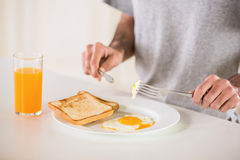 Breakfast. Close-up of man in grey t-shirt eating omelet and drinking juice for breakfast on white background Royalty Free Stock Image