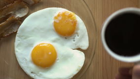 Breakfast of coffee, bacon and eggs on a wooden table. Top view. stock video footage
