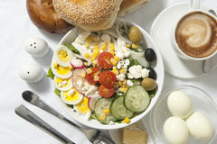 Breakfast with coffee, bagels, salad and eggs stock images