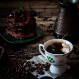 Breakfast: coffee, chocolate pancakes. With cherry jam. On wood background with coffee beans, recipe sheet and burlap Stock Images