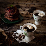 Breakfast: coffee, chocolate pancakes. With cherry jam. On wood background with coffee beans, recipe sheet and burlap bag Stock Image