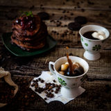 Breakfast: coffee, chocolate pancakes. With cherry jam. On wood background with coffee beans, recipe sheet and burlap bag Stock Photography