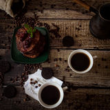 Breakfast: coffee, chocolate pancakes. With cherry jam. On wood background with coffee beans, recipe sheet and burlap bag Stock Photos