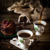 Breakfast: coffee, chocolate pancakes. Breakfast: pouring coffee, chocolate pancakes with cherry jam. On wood background with coffee beans, recipe sheet and Stock Image