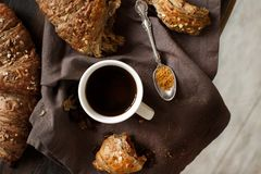 Breakfast with coffee and croissant. On a wooden background top view stock image