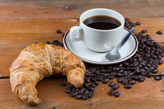 Breakfast with coffee and croissant. On wooden table Stock Photos