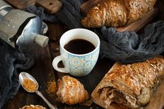 Breakfast with coffee and croissant. On a dark wooden background close up royalty free stock photos