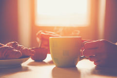 Breakfast with coffee and croissant. Fresh breakfast with hot coffee and croissant in morning sunlight Royalty Free Stock Images