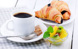 Breakfast. Coffee with croissant and fruit. Breakfast. Black coffee, fresh, crackling croissant with chocolate and fruit Stock Photography