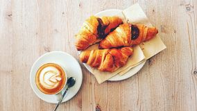 Breakfast with coffee and croissant. Having breakfast on wooden table with chocolate croissant and cappuccino, typical italian Royalty Free Stock Image
