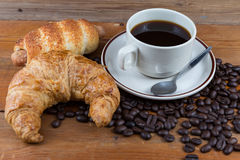Breakfast with coffee, croissant and sausage dough. On wooden table Stock Photography