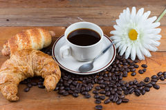 Breakfast with coffee, croissant and sausage dough. On wooden table Stock Image