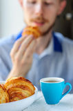 Breakfast with coffee and croissant with young man on background. Blurred young man eats his breakfast, coffee, croissant Stock Photo