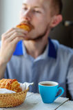 Breakfast with coffee and croissant with young man on background. Blurred young man eats his breakfast, coffee, croissant Royalty Free Stock Images