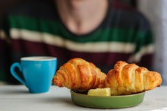 Breakfast with coffee and croissant with young man on background. Blurred young man eats his breakfast, coffee, croissant Royalty Free Stock Image