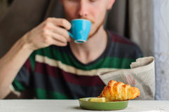 Breakfast with coffee and croissant with young man on background. Blurred young man eats his breakfast, coffee, croissant and reads newspaper Royalty Free Stock Images