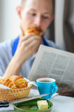 Breakfast with coffee and croissant with young man on background. Blurred young man eats his breakfast, coffee, croissant and reads newspaper Royalty Free Stock Photography