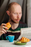 Breakfast with coffee and croissant with young man on background. Blurred young man eats his breakfast, coffee, croissant and reads newspaper Royalty Free Stock Photo