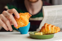 Breakfast with coffee and croissant with young man on background. Blurred young man eats his breakfast, coffee, croissant and reads newspaper Stock Photo