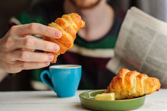 Breakfast with coffee and croissant with young man on background. Blurred young man eats his breakfast, coffee, croissant and reads newspaper Stock Photos