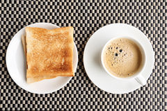 Breakfast. Coffee cup and bread on the plate  mat Stock Image