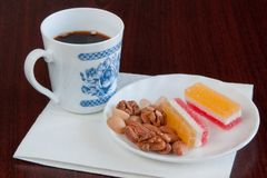 Breakfast with the coffee. Coffee cup, marmalade and nuts on the white plate Royalty Free Stock Images