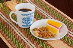 Breakfast with the coffee. Coffee cup, marmalade and nuts on the white plate Royalty Free Stock Photos