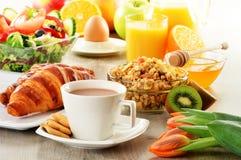 Breakfast with coffee, juice, croissant, salad, muesli and egg Stock Image