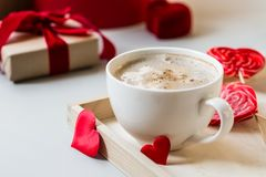 Breakfast coffee love heart red rose setting with white mug and gift box in Valentine`s day setting. Romantic breakfast coffee for Valentines day surprise for Stock Image