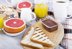 Breakfast with coffee and orange juice. Grapefruit, toast and chocolate spread Royalty Free Stock Images