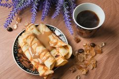 Breakfast with coffee and pancakes topped with sweet sauce on a wooden table stock photos