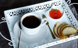 Breakfast of coffee and red caviar. Breakfast of black coffee in a white cup on a white tray red caviar and bread Royalty Free Stock Photos