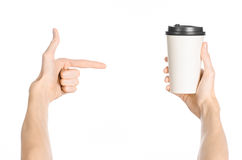 Breakfast and coffee theme: man's hand holding white empty paper coffee cup with a brown plastic cap isolated on a white backgroun. D in the studio, advertising royalty free stock photos