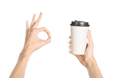 Breakfast and coffee theme: man's hand holding white empty paper coffee cup with a brown plastic cap isolated on a white backgroun. D in the studio, advertising royalty free stock image